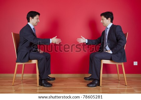 Handshake agreement between two twin businessman sitting in a chair next to a red wall