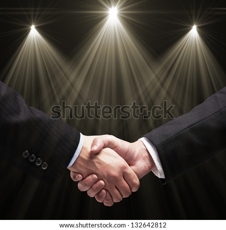 handshake and light lamps on white background - stock photo