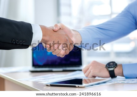 Handshake and partnership. Two Confident businessman sitting at the negotiating table in the office and shaking hands close-up view of hands. Business people dressed in formal wear - stock photo