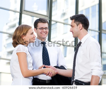 Handshake between business partners in front of office building. Happy people smiling and looking at each other while signing new international contract between companies.
