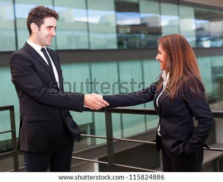 Handshake between businessman and businesswoman at modern office - stock photo
