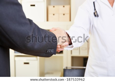 Handshake between doctor and patient in an office - stock photo