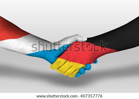 Handshake between germany and luxembourg flags painted on hands, illustration with clipping path.