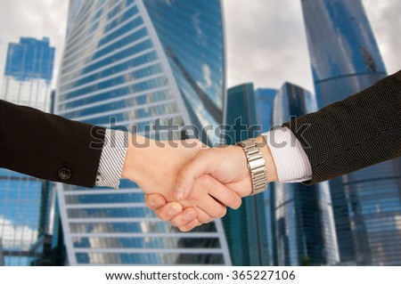 Handshake between man and a woman with skyscrapers in the background - stock photo