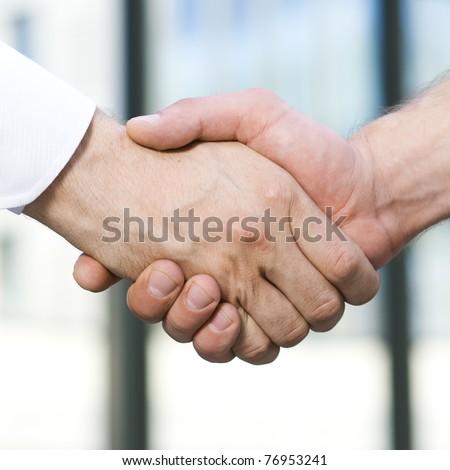 Handshake between office workers outdoor - stock photo