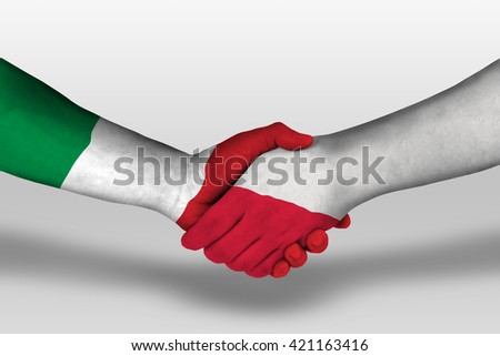 Handshake between poland and italy flags painted on hands, illustration with clipping path. - stock photo