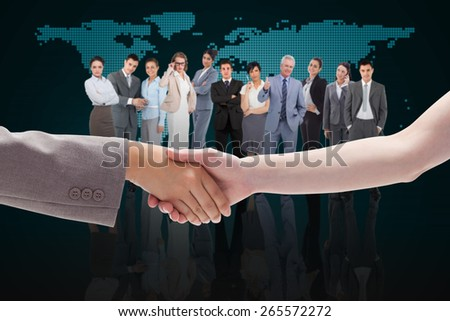 Handshake between two women against blue world map - stock photo