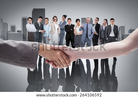 Handshake between two women against cityscape - stock photo