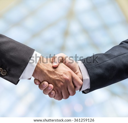 Handshake. Closeup shot of hands. The business center on the background. - stock photo