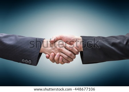 Handshake - Hand holding of two business men on gradient background