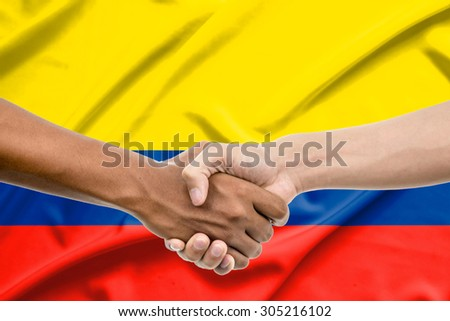 Handshake - Hand holding on colombia flag background - stock photo