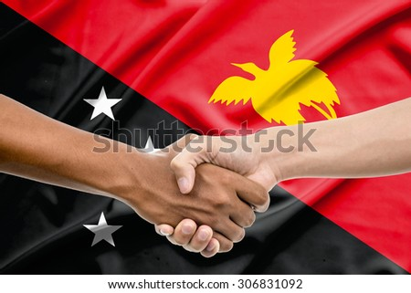 Handshake - Hand holding on papua new guinea flag background - stock photo