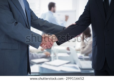 Handshake in agreement against young business people in board room meeting - stock photo