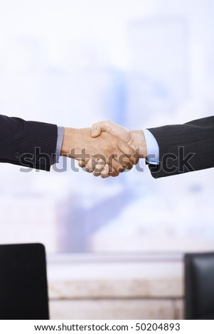 Handshake in closeup in business situation in office.