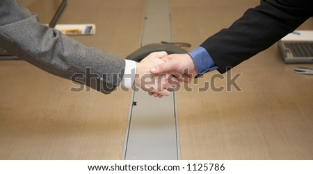 Handshake in conference room, computers and conference phone in the background - stock photo