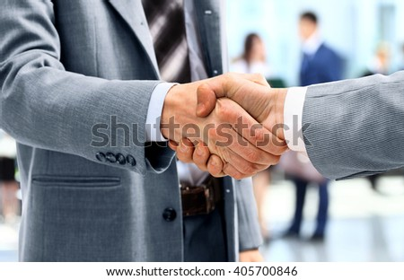 Handshake in front of business people - stock photo