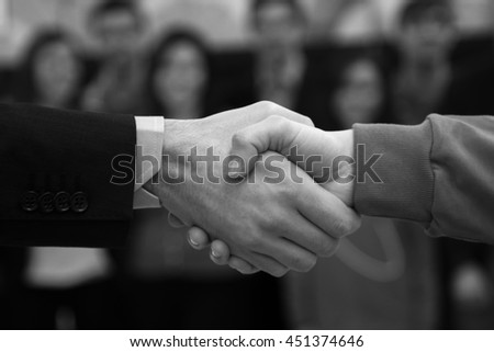 Handshake, manager and worker, with workers group  blurred in the background - stock photo