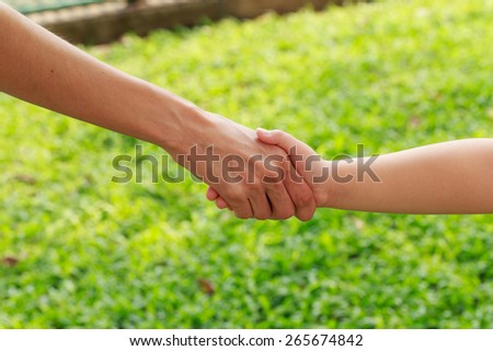 Handshake mother and daughter on grass background