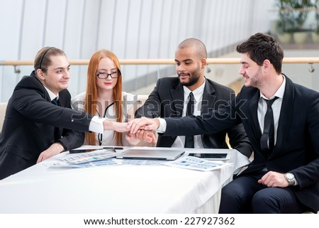 Handshake of business colleagues. Four smiling successful businessmen sitting at table in office while discussing their business doings. Young people talking in office - stock photo