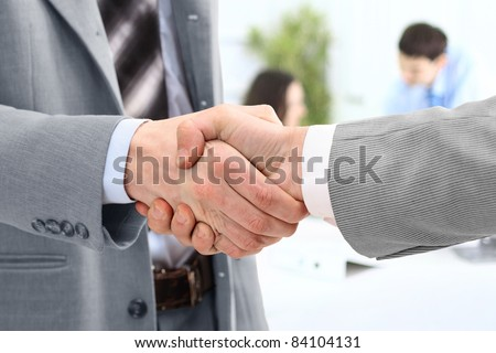 handshake of business partners after striking deal - stock photo