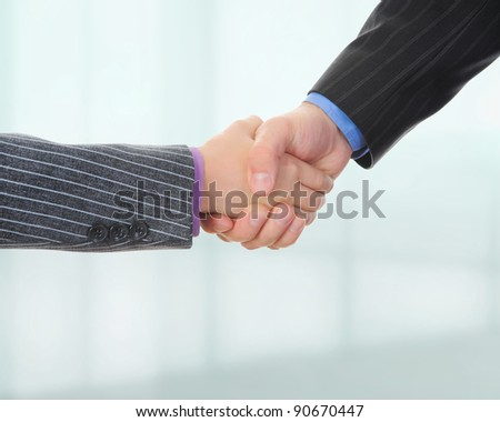 Handshake of business partners on the background of an office building - stock photo