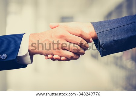 Handshake of businessman and businesswoman,  vintage tone - greeting, dealing, merger and acquisition concepts - stock photo