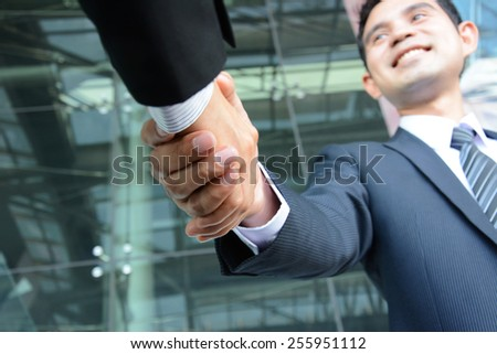 Handshake of businessman with smiling face - hands focused - stock photo