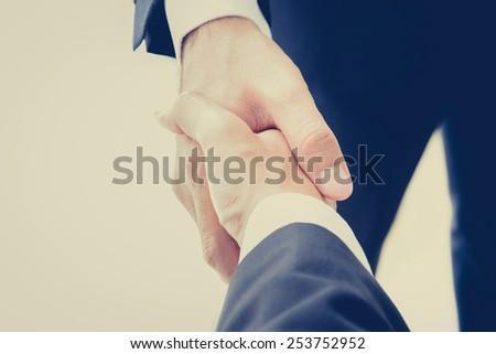 Handshake of businessmen in vintage (retro) color effect - success, congratulation, greeting & business partner concepts - stock photo