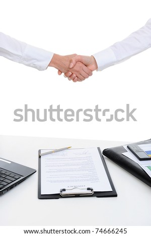 Handshake of two business partners after signing a contract. Focus on the documents - stock photo