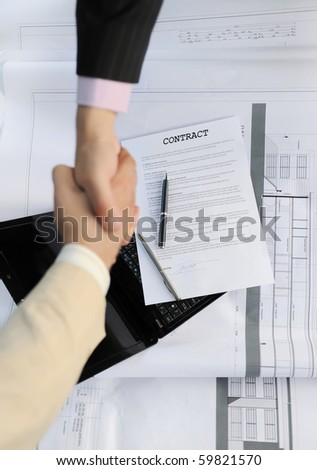 Handshake of two business partners. Focus on the documents - stock photo