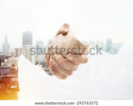 handshake on city background, double exposure - stock photo