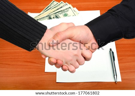 Handshake on Envelope with a Money and Empty Paper - stock photo