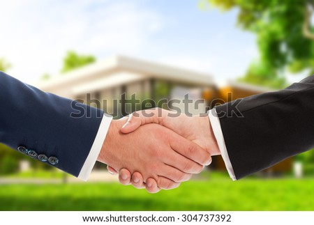 Handshake on house outdoor background as real estate deal or sale concept - stock photo