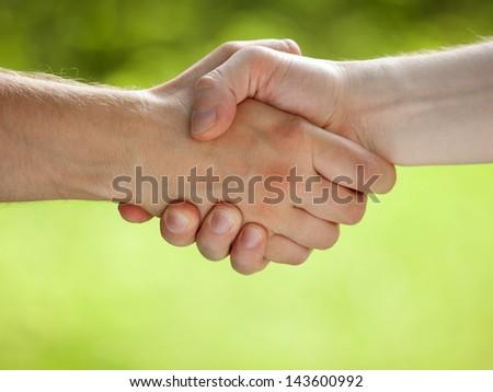 Handshake on light green eco background - stock photo