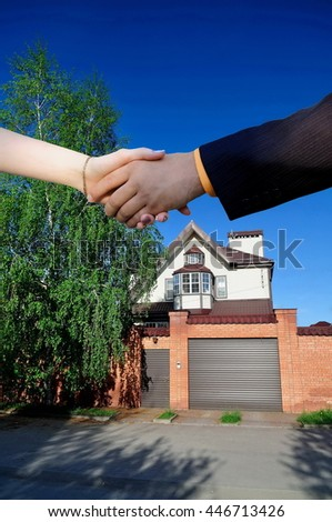 handshake on the background of a new home - stock photo