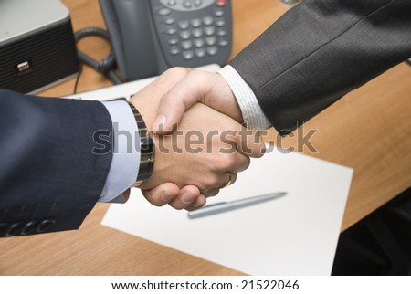handshake over paper and blurry keyboard in the background - stock photo