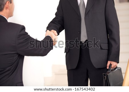 Handshake. Two business men in formalwear handshaking on staircase