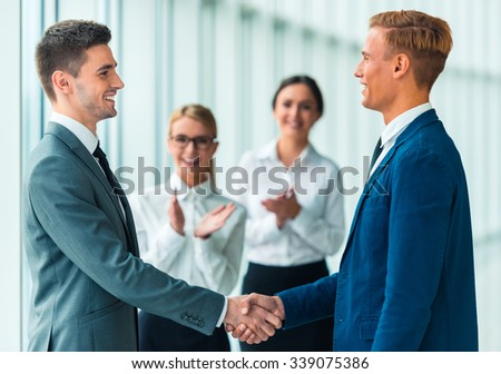 Handshake two business people on the background of their colleagues in the office