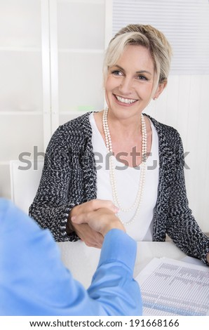 Handshake under two business woman at the office. - stock photo
