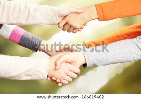 Handshakes on bright background - stock photo
