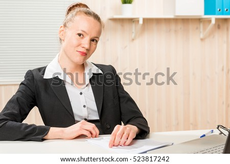 handsome accountant in a jacket at office working