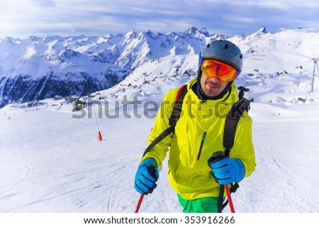 Handsome active man with sky in helmet and goggles. Standing on sloap in Alps mountains - stock photo