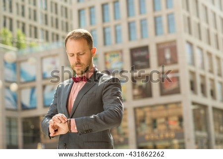 Handsome adult businessman looking on watch in downtown