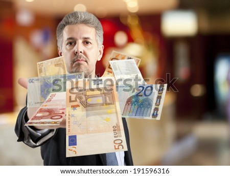 Handsome adult businessman throwing euro - stock photo