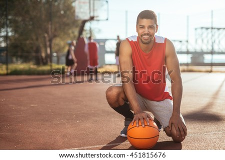 Handsome african american basketball player posing with a ball. - stock photo