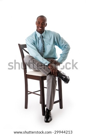 Handsome African American business man smiling sitting on chair, wearing sea green shirt and gray pants, isolated - stock photo