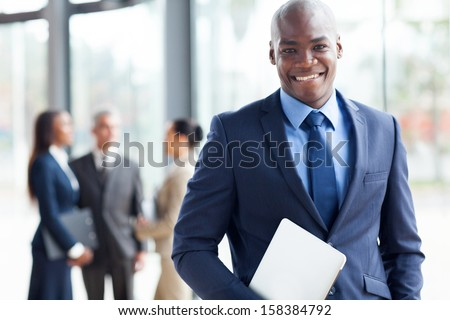 handsome african american businessman with laptop computer in office - stock photo