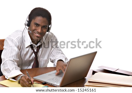 Handsome African-American businessman working on a laptop and wearing a headset - stock photo