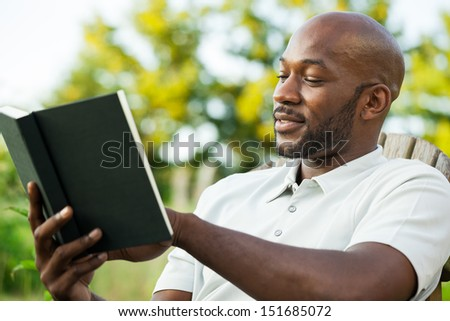 Handsome African American man in his late 20s reading a book at the park on a summer day