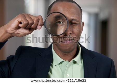 Handsome African American man looking through a large magnifying glass - stock photo